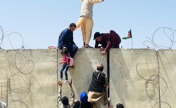 People from Afghanistan try to flee by climbing over a wall